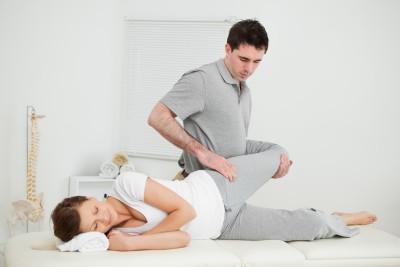 Bein einer Frau, die von einem Chiropraktiker in einem medizinischen Raum manipuliert