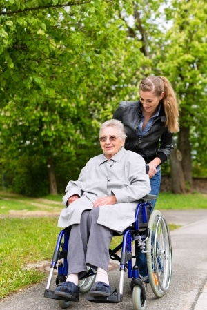 14727941 - young woman is visiting her grandmother in nursing home having a walk with here in a wheelchair